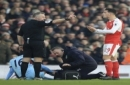 Burnley's Steven Defour, below, is left injured on the ground after a challenge from Arsenal's Granit Xhaka, right, for which he received a red card, during their English Premier League soccer match at The Emirates Stadium, London, Sunday, Jan. 22