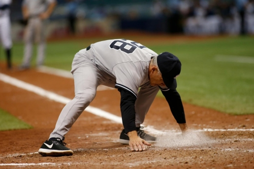 Joe Girardi cleans home plate two days after covering it in dirt