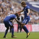 Chelsea's Marcos Alonso, right, celebrates with teammate Chelsea's Victor Moses after scoring the opening goal of the game during their English Premier League soccer match between Tottenham Hotspur and Chelsea at Wembley stadium in London, Sunday