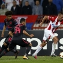 Red Star's Nenad Krsticic, right, challenges for the ball with Arsenal's Francis Coquelin, center, and Reiss Nelson during the Europa League group H soccer match between Red Star and Arsenal on the stadium Rajko Mitic in Belgrade, Serbia, Thursday