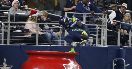 Seahawks DB Justin Coleman hops into a Salvation Army kettle to celebrate his pick-six in a 21-12 win over Dallas