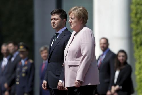 Merkel luce vacilante y temblorosa en ceremonia en Berlín