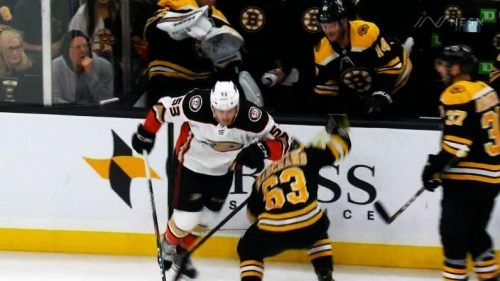 Brad Marchand ducks under an elbow attempt by Maxime Comtois